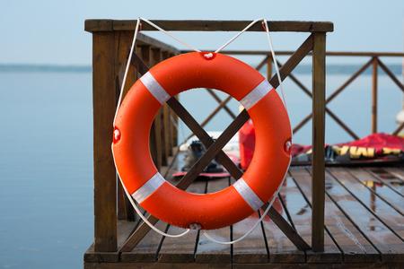 Marine lifebuoy on fence, on water background Standard-Bild