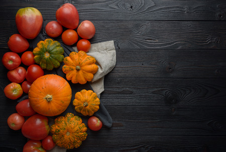 Composition of pumpkins and tomato on a wooden background