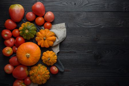 Zusammensetzung von Kürbissen und Tomaten auf einem hölzernen Hintergrund