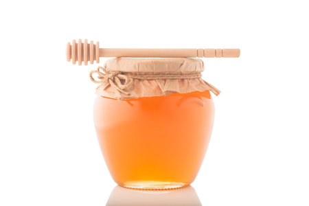 Glass jar full of honey and wooden stick on it isolated on a white background