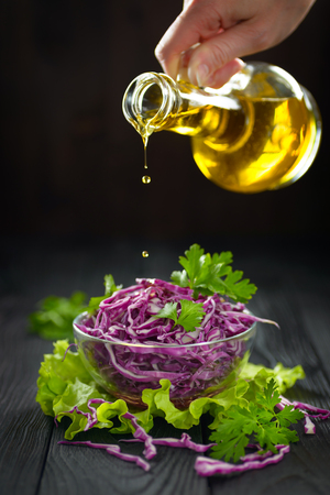 Vegetarian red cabbage salad pouring with olive oil, concept of a healthy diet
