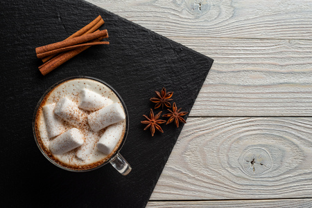 coffee with milk and marshmallow with cinnamon and anise on wooden background top view Zdjęcie Seryjne