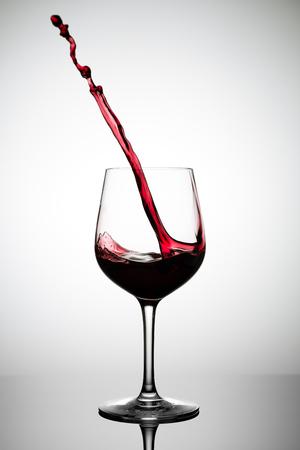 vino rosso che schizza da un bicchiere