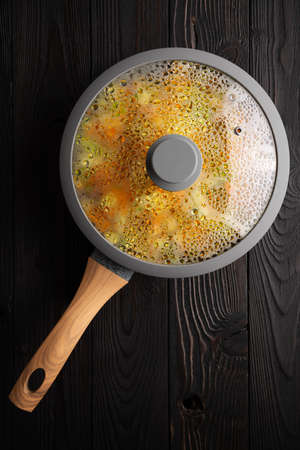 fresh stewed vegetables in a frying pan on a wooden background, flat lay Banco de Imagens