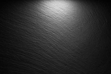 textured black slate background with spot of light