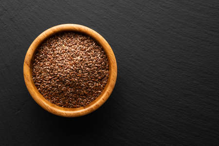 flax seeds in a wooden bowl on a slate background, top view Banco de Imagens