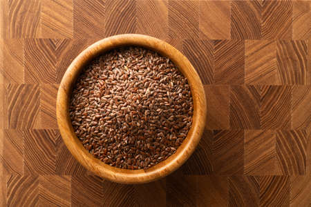 flax seeds in a wooden bowl on a wooden background, top view