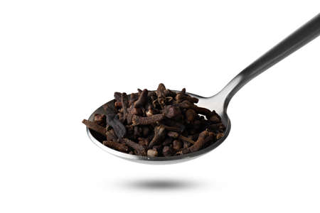 fragrant spice clove in metal spoon isolated on white background Banco de Imagens