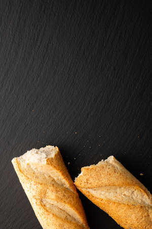 broken in half baguette on a stone background, top view Banco de Imagens
