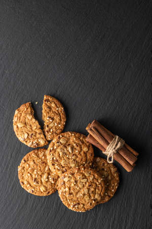 oatmeal cookies with grains and cinnamon on a stone background