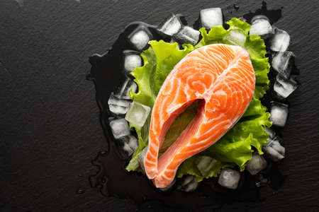 chilled salmon steak in lettuce and ice on a stone background, top view, place for text