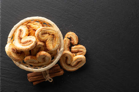 crispy puff pastry with sugar and cinnamon on a black stone background, top view, place for text