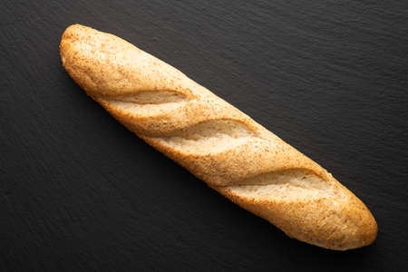 french baguette with bran on a dark stone background