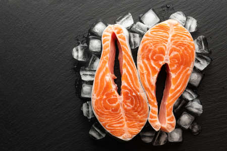 chilled salmon steak and ice on a stone background, top view, place for text Banco de Imagens
