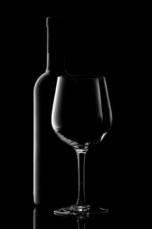 red wine bottle and wine glass isolated on black background