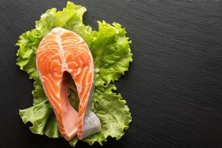 fresh salmon steak on lettuce leaf, stone background, flat lay, place for text