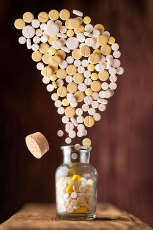 various pills fly out of a glass jar in the form of letter D on a wooden background