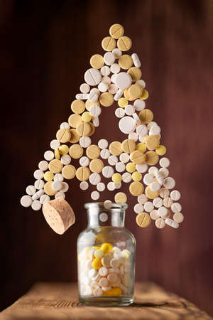 various pills fly out of a glass jar in the form of letter A on a wooden background