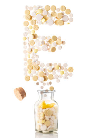 various pills fly out of a glass jar in the form of letter E, isolated on white background Banco de Imagens