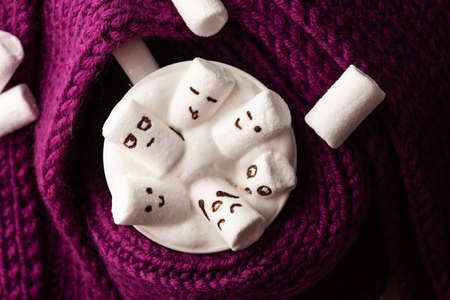 marshmallows with painted faces in a mug with cappuccino wrapped in a knitted scarf