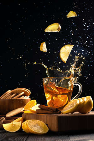 falling slices of lemons into a mug with hot tea, tea splashes in different directions.