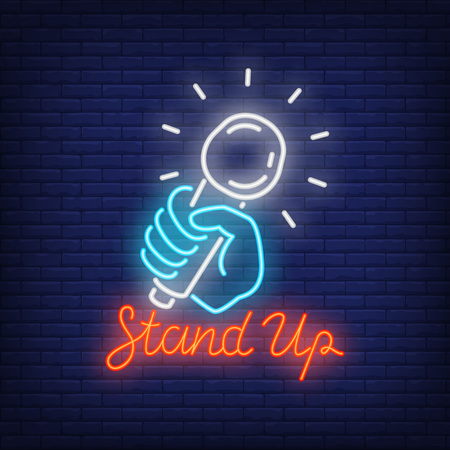 Stand up neon sign, microphone in human hand on brick wall background. Night bright advertisement vector illustration in neon style for comedy show.