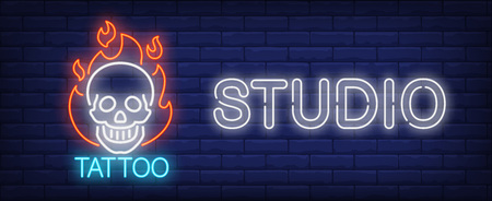 Tattoo studio neon sign. Smiling scull on fire and big inscription on dark brick wall. Vector illustration in neon style for tattoo salon or luminous advertisement