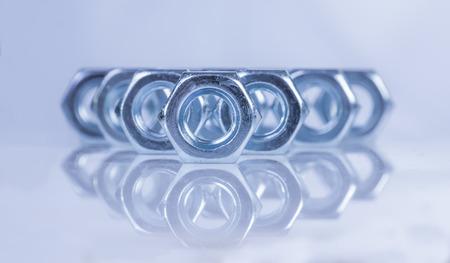 herramientas de trabajo: tuercas de acero cromado sobre superficie reflectante