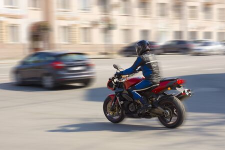 Biker rides on a city road on a sunny day. Stock Photo