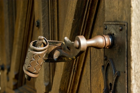 view of a wooden doorway: unusual old  metal handle on wooden door Stock Photo