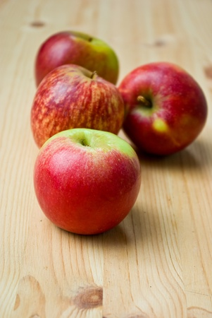 red ripen apples on wooden table close up photo