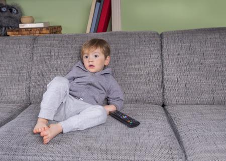 リモート コントロールとソファに掛かっている幼児