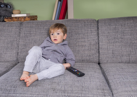 kids: toddler hanging on the couch with a remote control