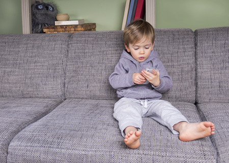 little boy using a mobile phone sitting on the couch