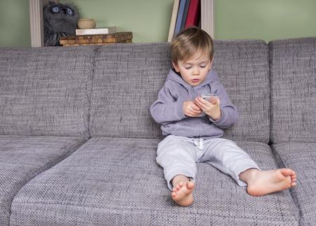 radiacion: niño pequeño usando un teléfono móvil que se sienta en el sofá