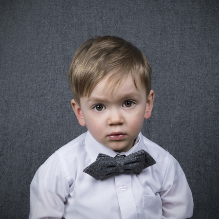 two year old: two year old boy looking straight into the camera wearing a grey bowtie
