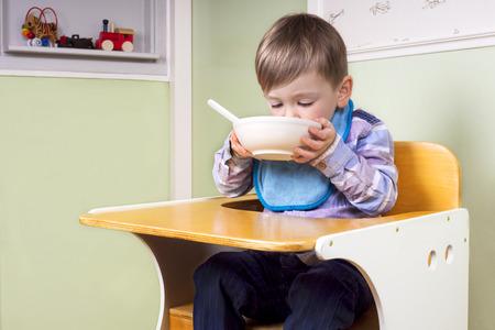 jardin de infantes: ni�o que se sienta en su silla bebiendo de un taz�n