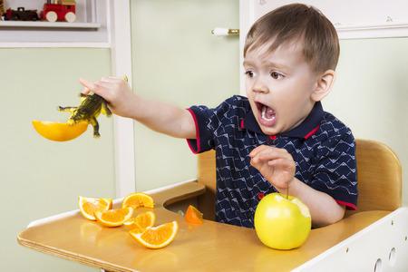 jardin de infantes: ni�o que se sienta en una silla de jugar durante el tiempo de la fruta