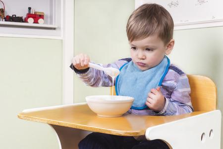 jardin de infantes: Ni�o que mira su comida sin abrir el apetito Foto de archivo