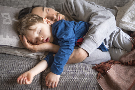 portrait of father and son fallen asleep together on the couch