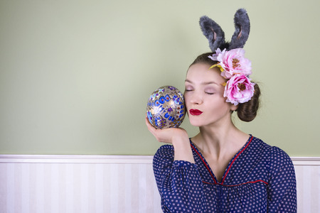 bunny ears: Young lady with bunny ears holding a large easter egg Stock Photo