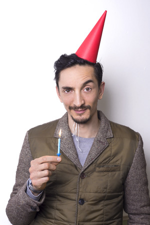 dubious: man in his thirties holding a birthday candle and looking dubious. Stock Photo