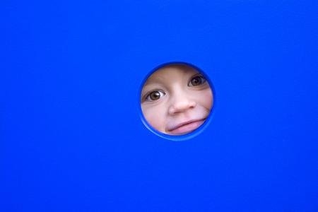 cute little boys face peeking through a hole of a playground equipment. Stock Photo
