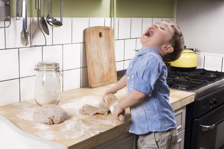 Two year old boy rolling dough in the kitchen and acting silly.