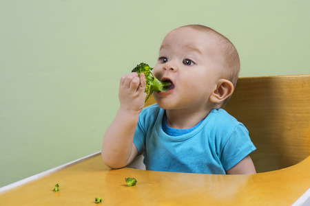 adorable baby eating broccoli