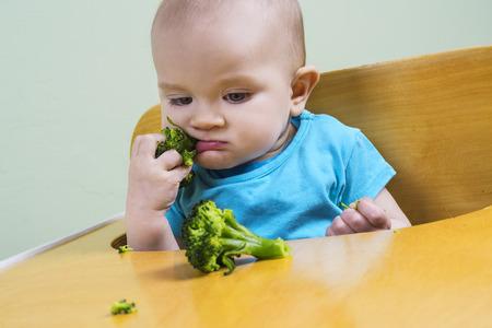 Funny baby tasting broccoli