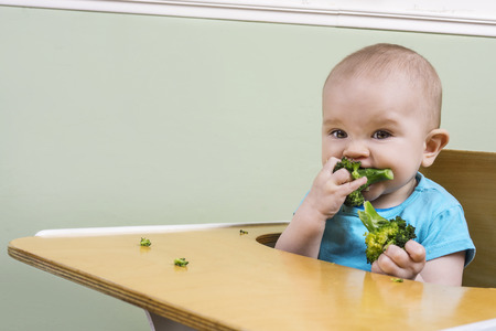 child food: funny baby trying broccoli for the first time
