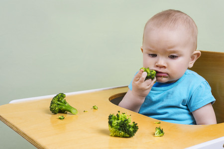 cute baby tasting broccoli
