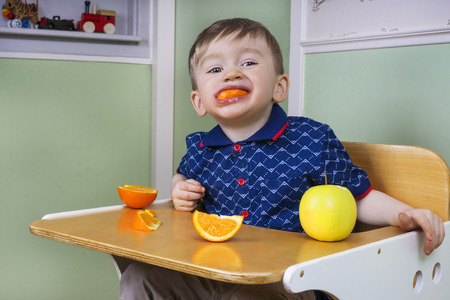 Toddler eating fruit and being naughty Stock Photo