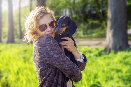 Beautiful blonde holding her dog. Stock Photo